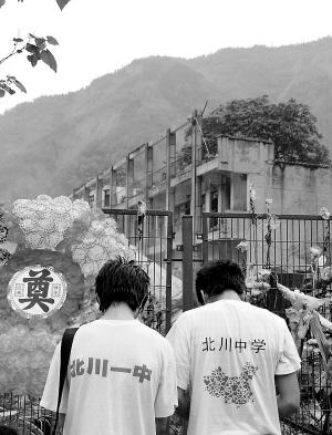 两名北川中学的毕业生在老北川中学遗址前致哀. 新华社记者 郑晓奕图片