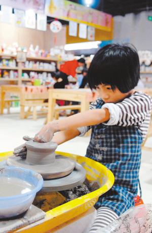 6月1日,许多小朋友来到三亚市明珠广场的手工作坊学习制作陶艺.