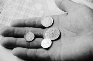 刘大军/刘大军展示老人给的游戏币、港币、日币和一分钱硬币。新华社发