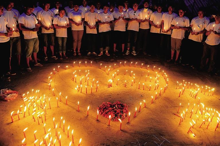 在云南鲁甸县龙头山镇骡马口,人们点燃蜡烛,悼念逝者.