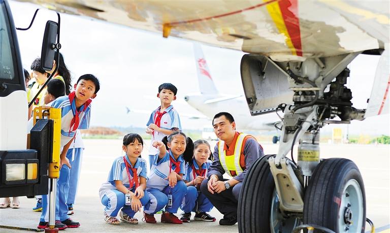 图为小学生在飞机起落架下观看飞机的细节.本报记者 苏建强 摄