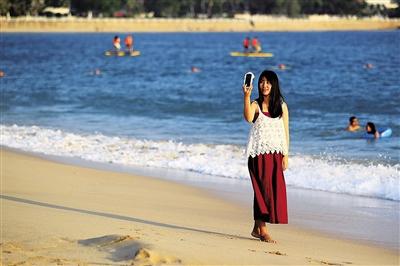 游客在三亚大东海海边留影.本报记者 武威 摄