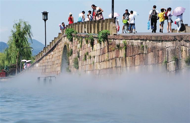 --> 7月27日,游客在杭州西湖断桥享受人造喷雾带来的清凉。 当日起,因杭州持续晴热高温和应广大游客的要求,西湖断桥每日上午9点30分至10点开启喷雾装置,让游客享受人造喷雾带来的清凉。 新华社发(吴煌 摄)-->
