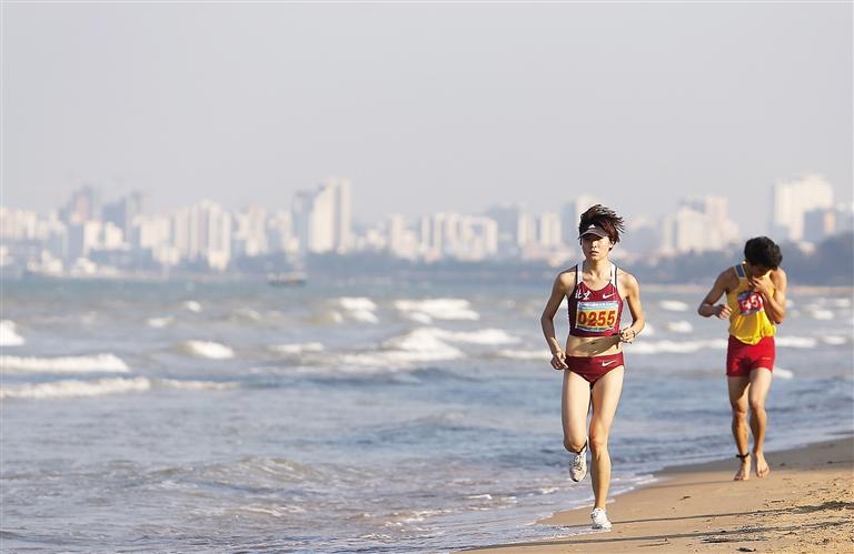 参加沙滩马拉松赛的选手在海口西海岸海边奔跑