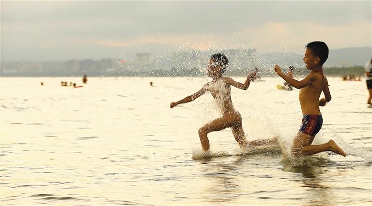 小朋友在三亚湾海边戏水玩耍.本报记者 武威 特约记者 陈文武 摄