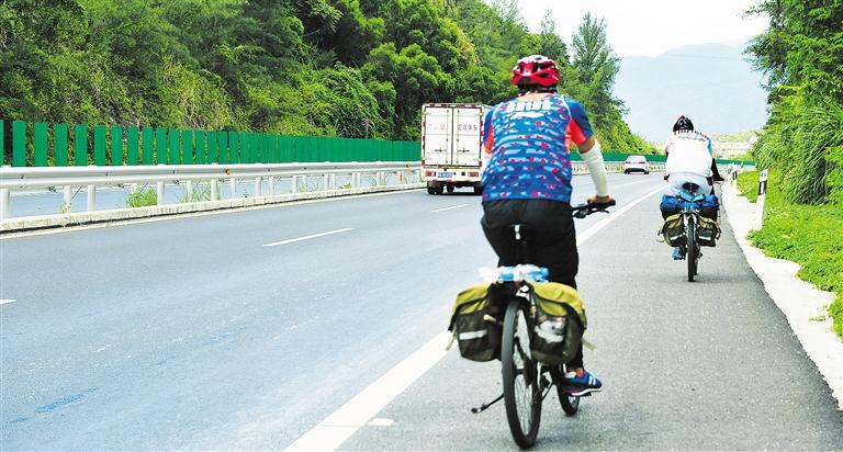 记者在环岛高速东线万宁至三亚路段看到,一群又一群的骑行爱好者在