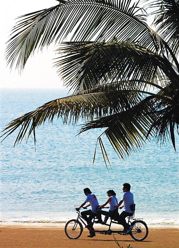 游客在三亚海边骑车玩乐.本报记者 张杰摄